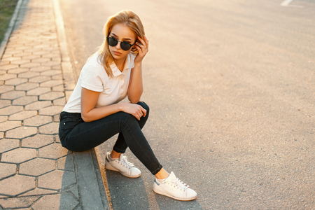 Pretty woman in fashion sunglasses in a white polo shirt and black jeans with white shoes sits on the asphalt at sunset