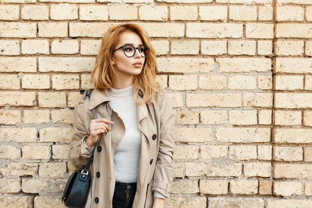 Young beautiful woman in glasses and a coat stands near a brick wall and looks aside Banco de Imagens