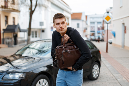 Young man stole a leather bag on the background of a car Stock Photo