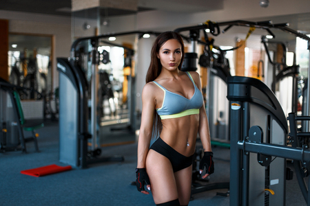 mooie jonge vrouw met een sexy lichaam in een sport-BH en zwarte slipje treinen in de sportschool