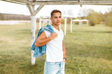 Handsome man in a white T-shirt with a jeans jacket outdoors Banco de Imagens - 82082303