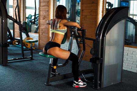 Mooie atletische vrouw met een sexy lichaam treint in de sportschool. Het concept van actieve levensstijl Stockfoto