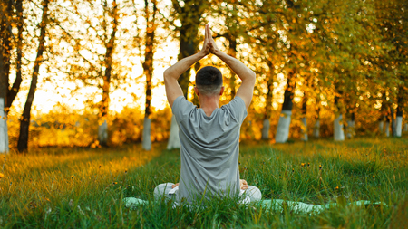 Man meditating practicing yoga in the park at sunset. Healthy lifestyle Stock Photo