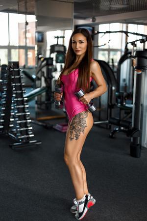 Sexy jonge vrouw met tatoeage in roze sportkleding met halters in de sportschool Stockfoto