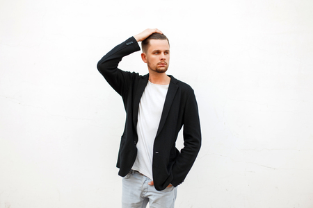 Beautiful stylish young man in trendy clothes near a white wall