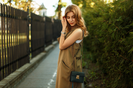 Beautiful young woman with a handbag in fashionable clothes walking outdoors