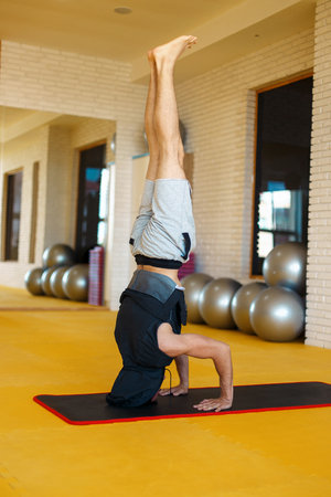Man doing yoga in headstand pose on mat in the gym Stock Photo