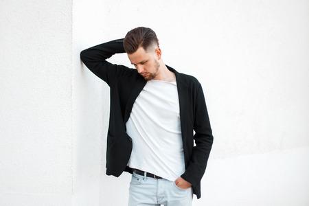 Fashionable handsome man in black stylish jacket posing near white wall