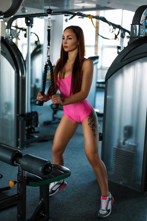 Mooie jonge vrouw met een tatoeage in roze sportkleding treinen in de sportschool