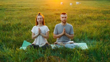 elasticidad: Pareja joven practicando yoga al aire libre al atardecer Foto de archivo