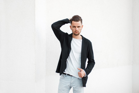 Handsome stylish young man in a black fashionable jacket and a white T-shirt posing near a white wall
