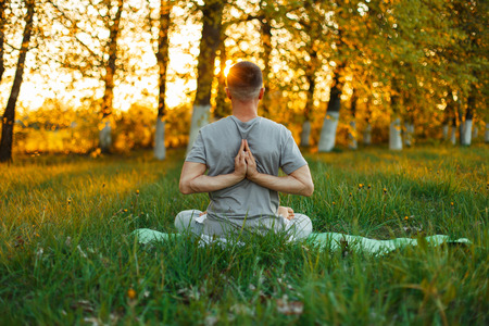 Man doing yoga in the park on a beautiful sunset. Healthy lifestyle