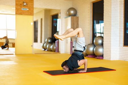 healthy man does yoga and a scorpion pose in the gym.