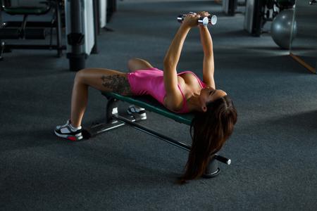 Mooie jonge sexy vrouw met een tatoeage in roze sportkleren pompen haar borst met halters in de sportschool