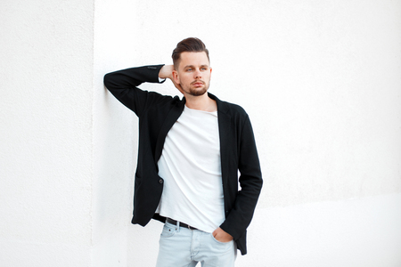 Young casual handsome businessman in stylish clothes near white wall Stock Photo