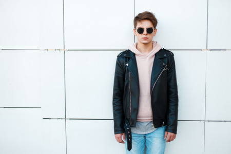 young man in a black leather jacket and a pink sweatshirt near a white wall. Vintage sunglasses aviator