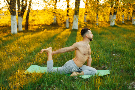 man practicing yoga in a park at beautiful sunset. Healthy lifestyle Stock Photo