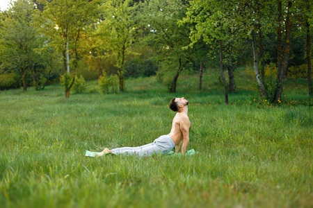 man practicing yoga on the grass in the park