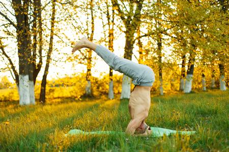 elasticidad: hombre practicando yoga en el parque en el césped al atardecer, estilo de vida saludable