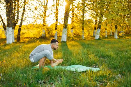 elasticidad: Hombre que practica yoga en un parque en la puesta del sol hermosa. Estilo de vida saludable