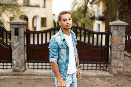 Stylish young guy in jeans vintage clothes near a wooden fence