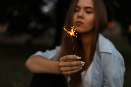 Beautiful burning Bengali fire with sparks in female hands