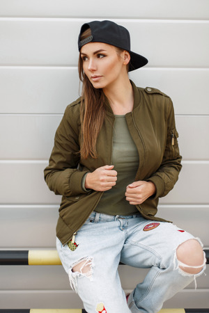 Beautiful stylish woman with freckles in a baseball cap in a fashionable green jacket with torn jeans near a silver wall