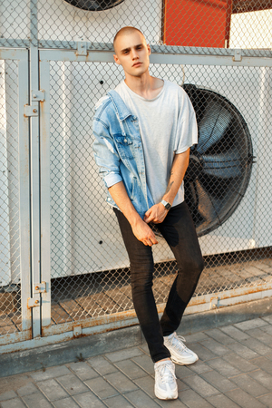 Fashionable young man in a denim jacket and a gray T-shirt with white shoes near the grid Stock fotó