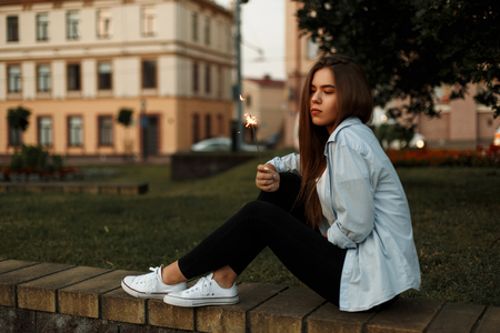 Young beautiful woman in a blue shirt and white sneakers with a sparkler rest in the park Stock Photo