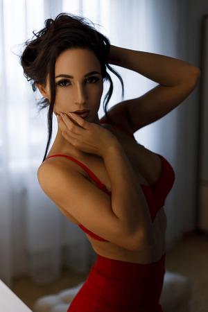 Hermosa joven con un peinado con un sexy pecho de silicona en un sujetador rojo y una falda roja en la habitación Foto de archivo - 85579898