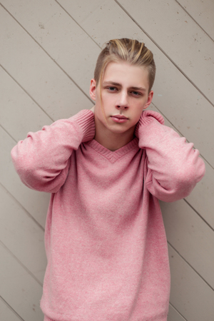 handsome young man with blond hair in a fashion pink sweater near a wooden wall Stock Photo