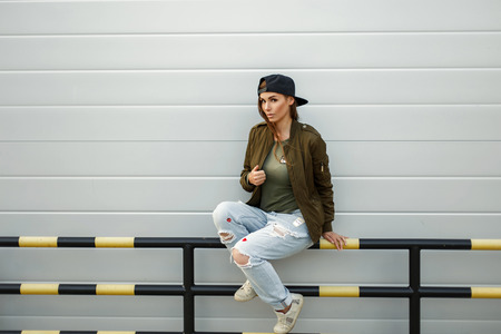 Beautiful fashionable woman in stylish street clothes with a baseball cap sits near a modern silvery wall Stock fotó