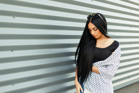 Beautiful brunette with long hair in fashionable clothes near a metal wall in the street Фото со стока