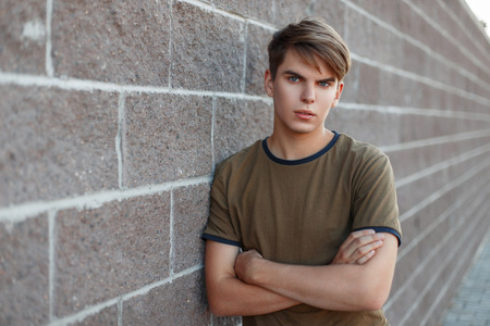 Portrait of a young handsome man in a classic T-shirt stands near a brick wall