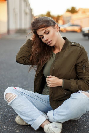 Beautiful young woman with freckles in trendy street clothes sitting on the asphalt Stock Photo