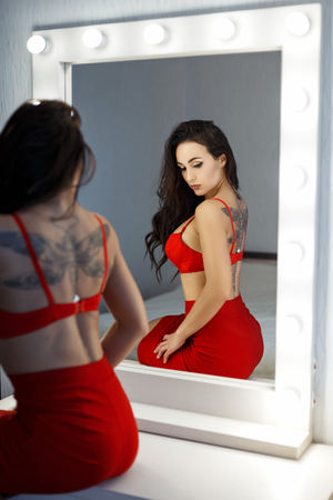 Beautiful sexy woman in a red bra and red skirt near a vintage mirror in the bedroom Stock Photo