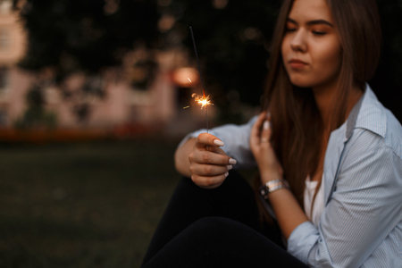 Beautiful young woman with sparkler resting on vacation