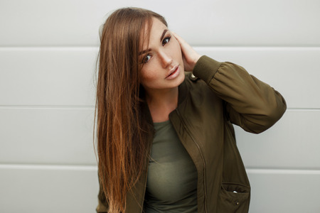 Beautiful woman with freckles in a green jacket and t-shirt near a modern wall