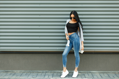 Beautiful stylish woman in a fashionable white cloak with a black T-shirt and blue jeans with a high waist with white shoes near the metal wall in the street
