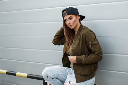 Fashionable young woman with freckles in stylish street clothes with a baseball cap sits near a metal wall