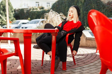 Young beautiful woman in fashionable autumn clothes in a black coat sits on a red chair in a cafe