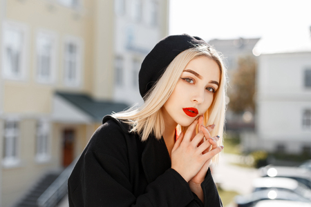 Fashionable portrait of a beautiful blonde woman in a black coat and a black beret on a sunny day
