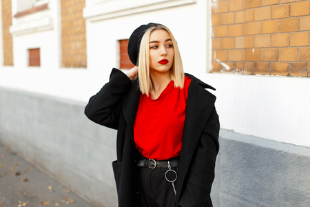 Beautiful blond woman with a beret in fashionable autumn clothes posing on the street