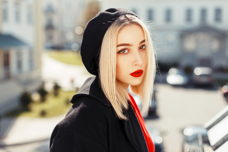 Portrait of a beautiful young blonde woman with red lips in a trendy black coat with a beret on a sunny day