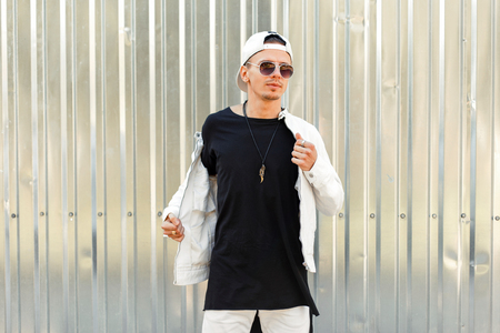 Stylish handsome man in a black T-shirt with a white jacket in fashion sunglasses near the metal wall