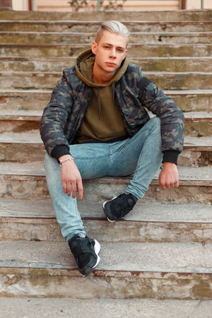 Stylish young man in a military jacket with a hoodie and jeans posing on the steps Stock Photo