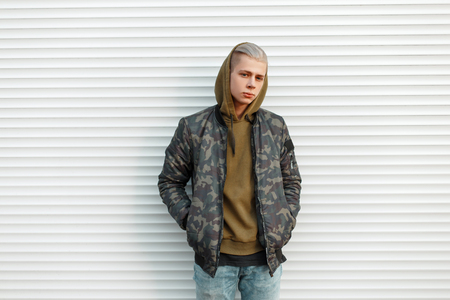 Handsome young man in a trendy military jacket with a hood near white metal blinds