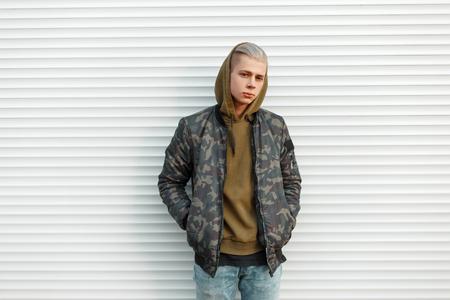 Knappe jonge man in een trendy militair jasje met een kap in de buurt van witmetalen jaloezieën Stockfoto - 90921624