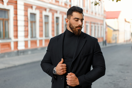 Fashionable man with a hairdo in a stylish black coat posing on the street Stock fotó