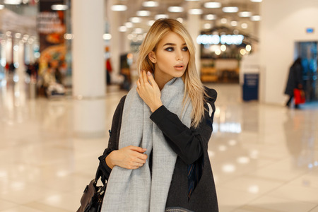 Beautiful fashionable girl in a stylish coat with a scarf and handbag in the mall Stock Photo